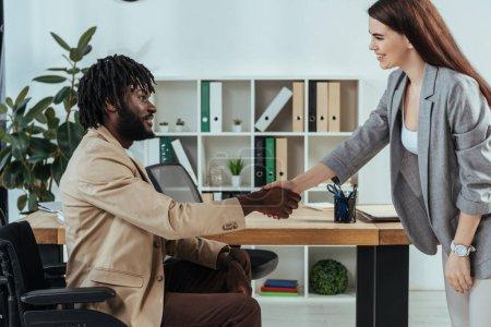Photo pour Employé et recruteur américain handicapé se serrant la main lors d'un entretien d'embauche dans son bureau - image libre de droit