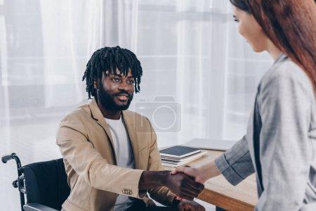 Photo pour Employé américain et recruteur africain handicapé se serrant la main et se regardant lors d'un entretien d'embauche - image libre de droit