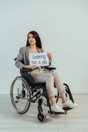 Photo for Disabled woman looking away and holding placard with looking for a job lettering on wheelchair isolated on white - Royalty Free Image