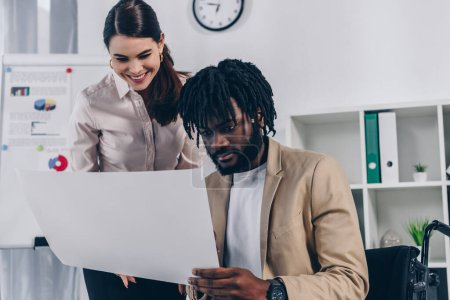 Positive recruiter and african american disabled employee looking at wove paper in office