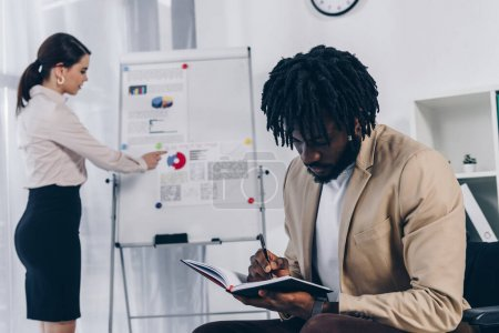 African american disabled employee writing in notebook with recruiter near flip chart in office