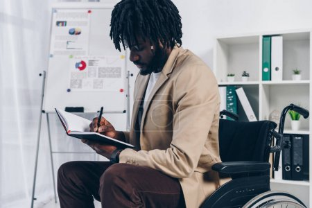 African american disabled employee on wheelchair writing in notebook in office