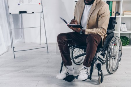 Photo for Cropped view of african american disabled employee on wheelchair writing in notebook in office - Royalty Free Image
