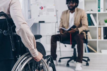 Photo for Cropped view of disabled recruiter on wheelchair and african american employee with notebook in office - Royalty Free Image
