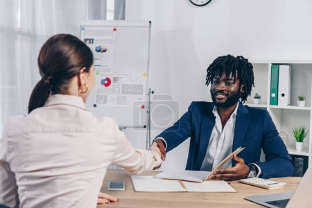 Photo for Selective focus of employee and african american recruiter looking at each other and shaking hands at table - Royalty Free Image