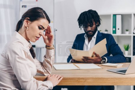 Stressed employee and african american recruiter with folder at table in office
