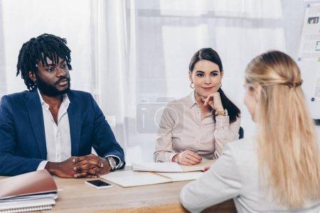 Photo pour Orientation sélective des recruteurs multiethniques menant une entrevue d'emploi avec un employé en poste - image libre de droit