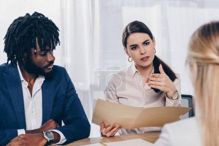 Photo pour Orientation sélective des recruteurs multiethniques menant une entrevue d'emploi avec un employé à table au bureau - image libre de droit