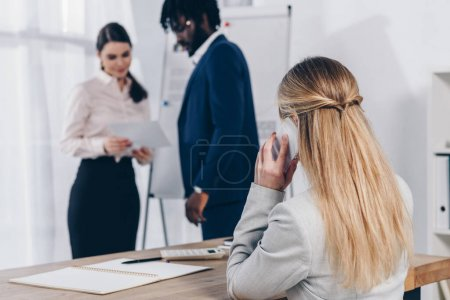 Photo for Multicultural recruiters with paper near flip chart and employee talking on smartphone in office - Royalty Free Image