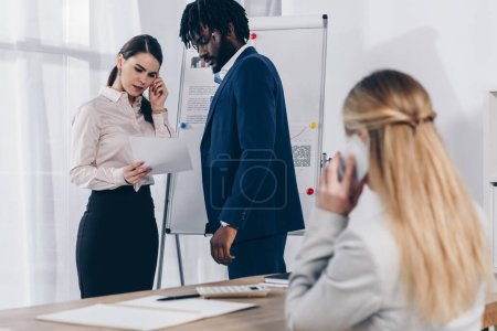 Photo for Selective focus of multicultural recruiters focused on paper near flip chart and employee talking on smartphone in office - Royalty Free Image