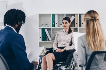 Selective focus of multiethnic recruiters conducting job interview with disabled employee in office