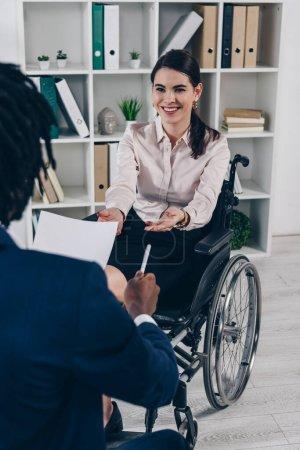 Photo pour Concentration sélective du recruteur afro-américain avec papier et stylo conduisant un entretien d'embauche avec un employé handicapé au bureau - image libre de droit