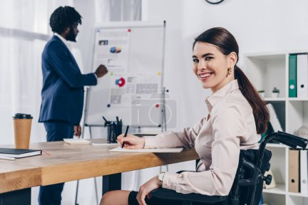 African american recruiter near flip chart and disabled employee writing in notebook, smiling and looking at camera in office