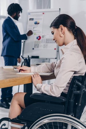 Photo pour Un recruteur africain américain près du tableau à feuilles mobiles et un employé handicapé qui écrit dans un carnet - image libre de droit