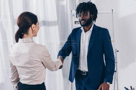 Foto de Empleador y empleado afroamericano estrechando la mano y mirándose mutuamente en el cargo. - Imagen libre de derechos