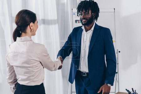 African american recruiter and employee shaking hands, smiling and looking at each other