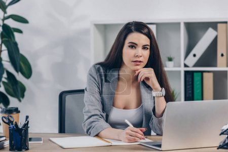 Photo for Recruiter looking at camera and writing in notebook near laptop in office - Royalty Free Image