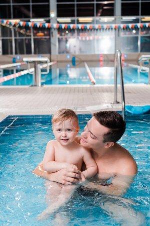 Photo pour Happy swim coach regardant un petit garçon mignon dans la piscine - image libre de droit