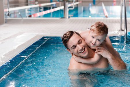 Photo for Happy toddler kid hugging swim coach in swimming pool - Royalty Free Image