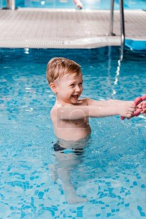 Photo pour Heureux tout-petit enfant jouer avec jouet en caoutchouc dans la piscine - image libre de droit