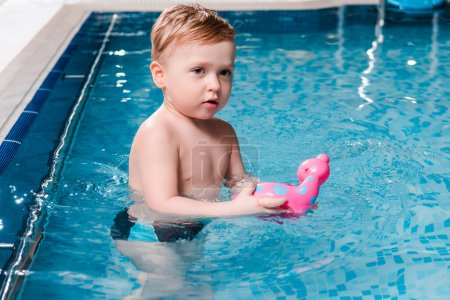 Photo for Cute toddler boy playing with rubber toy in swimming pool - Royalty Free Image