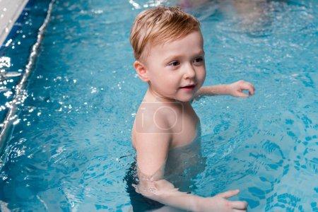 Photo pour Humide et adorable tout-petit garçon dans la piscine - image libre de droit