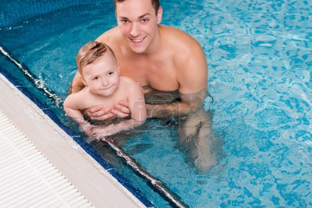 happy swim trainer holding in arms toddler boy while swimming in swimming pool