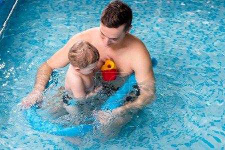 Photo pour Beau entraîneur de natation avec nouilles de piscine près de tout-petit enfant - image libre de droit