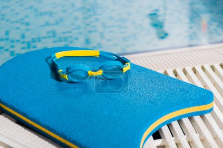 Photo pour Goggles on flutter board near swimming pool with blue water - image libre de droit