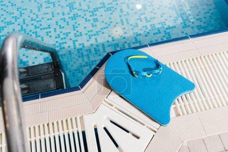 Photo pour Vue de dessus des lunettes de natation sur planche flottante près de la piscine - image libre de droit