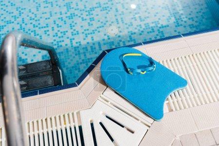 Photo pour Top view of swim goggles on flutter board near swimming pool - image libre de droit