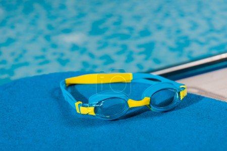 Photo pour Swim goggles on flutter board in swimming pool - image libre de droit