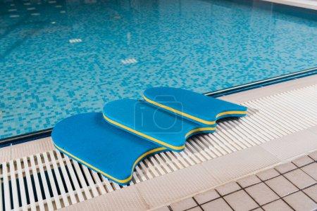 Photo pour Planches de flottement bleu près de la piscine dans le centre sportif - image libre de droit