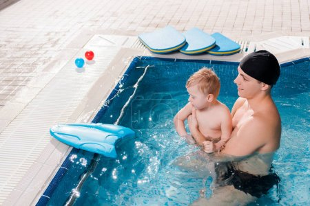 Photo for Side view of cheerful swim coach swimming with toddler kid in swimming pool - Royalty Free Image