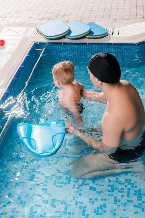 Photo pour Entraîneur de natation en bonnet de natation avec tout-petit enfant dans la piscine - image libre de droit