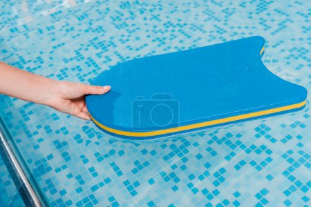 Photo pour Cropped view of woman touching flutter board in swimming pool - image libre de droit