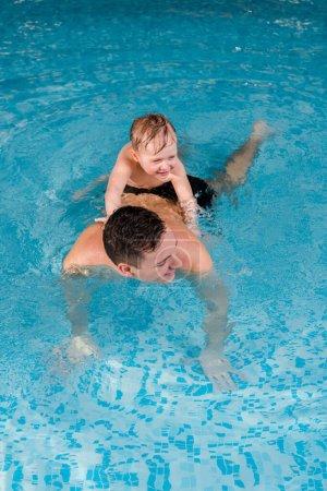 Photo pour Entraîneur de natation gai et petit garçon souriant s'entraînant dans une piscine - image libre de droit