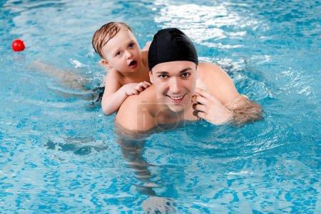 Photo pour Entraîneur de natation heureux et enfant en bas âge formation garçon dans la piscine - image libre de droit