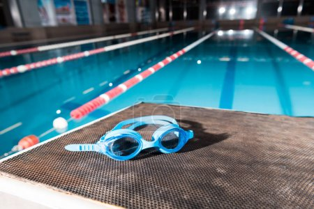 Photo pour Goggles near swimming pool with blue water - image libre de droit