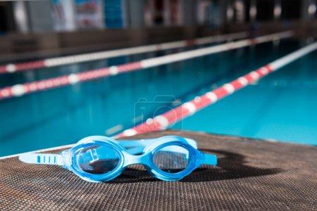 Photo pour Blue goggles near swimming pool in sports center - image libre de droit
