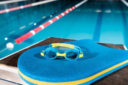 Photo pour Goggles on blue flutter board near swimming pool - image libre de droit