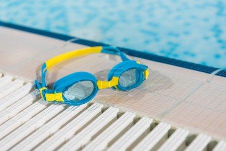 Photo pour Lunettes près de la piscine avec de l'eau bleue - image libre de droit