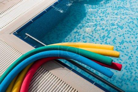 Photo pour Top view of colorful pool noodles near swimming pool - image libre de droit