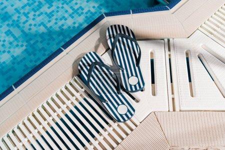 Photo pour Top view of flip flops near swimming pool with blue water - image libre de droit