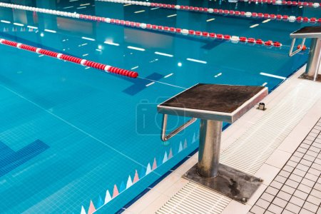 Photo pour Diving block near swimming pool with blue water - image libre de droit