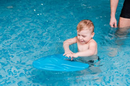 Photo for Cute toddler boy swimming with flutter board near swim coach - Royalty Free Image