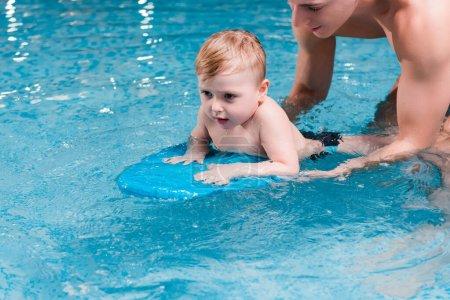 Photo pour Tout-petit garçon nageant avec planche flottante près de l'entraîneur de natation - image libre de droit