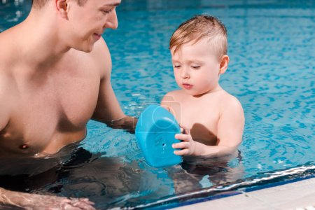 Photo pour Joyeux entraîneur de natation regardant un tout-petit jouer avec un bateau-jouet dans la piscine - image libre de droit