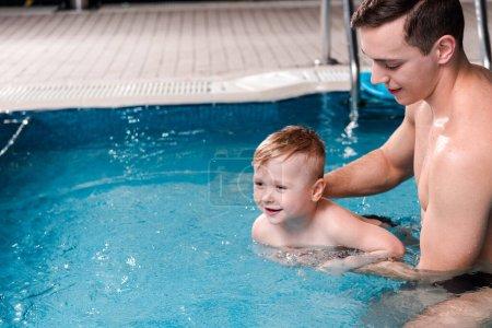 Photo pour Entraînement entraîneur de natation heureux tout-petit garçon dans la piscine - image libre de droit