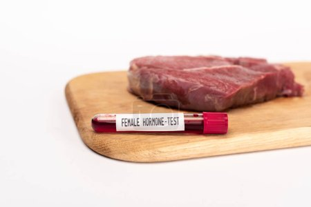 Photo for Selective focus of test tube with female hormone test on chopping board with raw meat isolated on white - Royalty Free Image